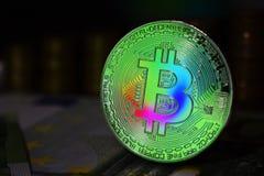 La moneda física del bitcoin del arco iris es BTC, preferiblemente verde del color imagenes de archivo