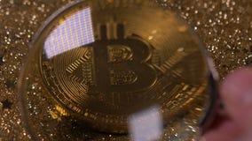 La moneda macra debajo de la lupa pertenece a Cryptocurrency Bitcoin metrajes