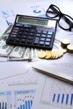 La moneta dei soldi di conteggio dell'uomo d'affari con i grafici commerciali del calcolatore ed i grafici riferiscono sulla tavo Immagine Stock