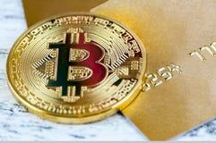 La moneta di oro Bitcoin si trova sulla carta assegni dell'oro Macro con sfuocatura Fotografia Stock