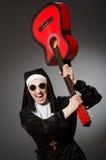 La monja divertida con jugar rojo de la guitarra Foto de archivo libre de regalías