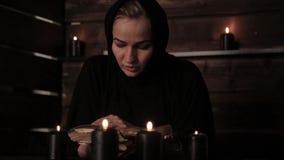 La monja está leyendo puntos culminantes del libro viejo la llama de una vela Concepto del cristianismo almacen de video