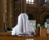 La monja se sienta en la iglesia Imagen de archivo libre de regalías