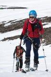 La montée d'alpiniste de ski de jeune femme sur la montagne sur des skis a attaché aux peaux s'élevantes Photographie stock libre de droits