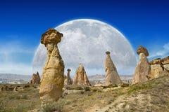 La montée de la pleine lune au-dessus du champignon bascule dans Cappadocia, Turquie Image stock
