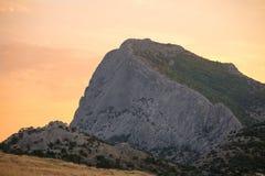 La montaña con la cuesta escarpada en el amanecer o la puesta del sol ligera palidece - el cielo rosado Foto de archivo libre de regalías