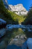 La montaña reflejó en el río de la garganta de Vikos en Grecia en otoño Fotos de archivo