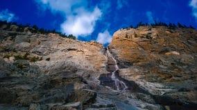 La montagna che si rivolta l'acqua della montagna della cascata delle nuvole e di luce solare cade Immagini Stock