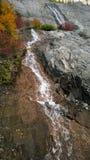 La montagna che si rivolta l'acqua della montagna della cascata delle nuvole e di luce solare cade fotografia stock libera da diritti