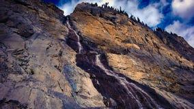 La montagna che si rivolta l'acqua della montagna della cascata delle nuvole e di luce solare cade Immagine Stock Libera da Diritti