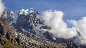 La montagna completa di estate con le nuvole e gli alberi Immagini Stock