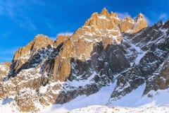 La montagna dell'inverno oscilla al tramonto alleggerito con i raggi del sole Immagine Stock Libera da Diritti