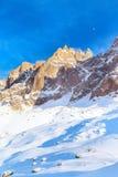 La montagna dell'inverno oscilla al tramonto alleggerito con i raggi del sole Immagini Stock