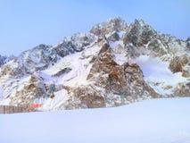 La montagna dell'inverno oscilla al tramonto alleggerito con i raggi del sole Immagini Stock Libere da Diritti