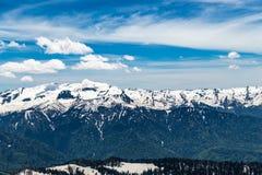 La montagna di Snowy completa con le nuvole nel cielo blu Immagine Stock