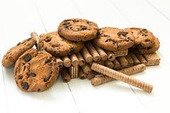 La montagna ha mescolato i rotoli della cialda del cioccolato, i biscotti e la cialda classica su una tavola bianca di legno Dolc immagine stock libera da diritti