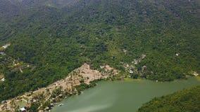 La montagna verde ha riguardato la vista aerea tropicale del lago e della foresta Vista del litorale del lago e dell'alta montagn archivi video