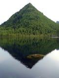 La montagne a à un formulaire de pyramide couvert du bois Photo libre de droits
