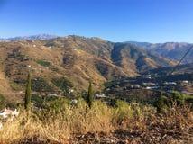La montagne et la colline s'étendent contre un ciel bleu clair Photo stock