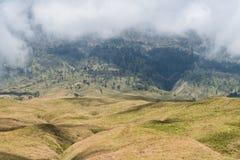 La montagne et la savane mettent en place avec le bas nuage au-dessus de la colline Montagne de Rinjani, île de Lombok, Indonésie Photo stock