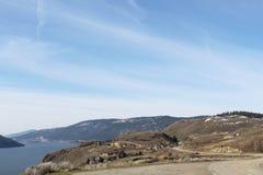 La montagne et le lac tôt de printemps aménagent en parc avec des maisons sur le flanc de coteau Images stock