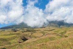La montagne et la savane mettent en place avec le bas nuage au-dessus de la colline Montagne de Rinjani Photos libres de droits