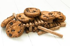 La montagne a m?lang? des petits pains de gaufre de chocolat, des biscuits et la gaufre classique sur une table blanche en bois D image libre de droits