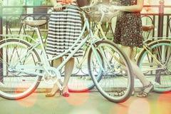 La monte et le voyage de femmes par la ville de vintage va à vélo Images libres de droits