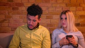 La montre africaine TV de type et son amie caucasienne blonde fonctionne avec le smartphone dans la maison confortable banque de vidéos