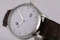 La montre argentée des hommes avec un cadran blanc, dans le sens horaire d'or, chronographe, avec un bracelet en cuir noir, d'iso images libres de droits