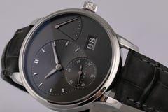 La montre argentée des hommes avec un cadran noir, chronomètre dans le sens horaire noir de chronographe avec un bracelet en cuir photographie stock