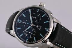 La montre argentée des hommes avec un cadran noir, dans le sens horaire bleu, chronographe, chronomètre, avec un bracelet en cuir images libres de droits