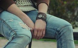 La montre-bracelet, avec beaucoup de bracelets en cuir brunissent sur les mains femelles Jeans Photos stock