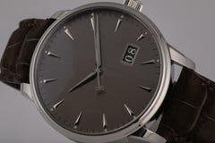 La montre des hommes avec le bracelet en cuir brun, cadran gris, dans le corps argenté, chronographe, dans le sens horaire noir,  photographie stock