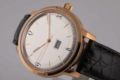 La montre des hommes avec le bracelet en cuir noir, cadran blanc, dans le corps d'or, chronographe, dans le sens horaire d'or, ch image stock
