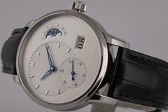 La montre des hommes avec le bracelet en cuir noir, le cadran blanc, dans le sens horaire bleu, le chronographe et le chronomètre photos libres de droits
