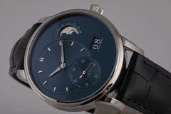 La montre des hommes avec le bracelet en cuir noir, cadran bleu, chiffres dans le sens horaire et romains gris, chronographe, chr photographie stock