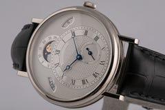 La montre des hommes avec le chronographe, le chronomètre sur le bracelet en cuir avec le cadran blanc, les nombres noirs et les  photo stock