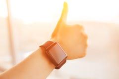 La montre intelligente en main montrant manie maladroitement vers le haut du signe Photos stock