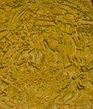 La morale thaïe de type découpent sur le mur en pierre. Photo libre de droits