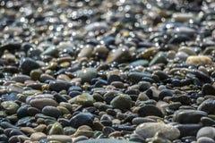 La morbidezza messa a fuoco ha offuscato l'immagine dell'peebles sulla spiaggia Immagine Stock