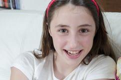 La morenita adolescente de la muchacha está mirando la cámara con sonrisa Imagen de archivo