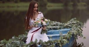 La morenita adorable joven con el pelo largo está sosteniendo el ramo mientras que flota en el barco misterioso de niebla cantida metrajes