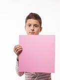 La morenita artística del muchacho del adolescente en un puente rosado con una hoja de papel rosada para las notas Foto de archivo libre de regalías