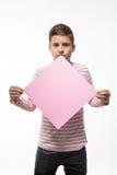 La morenita artística del muchacho del adolescente en un puente rosado con una hoja de papel rosada para las notas Imagen de archivo libre de regalías