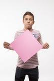 La morenita artística del muchacho en un puente rosado con una hoja de papel rosada para las notas Imágenes de archivo libres de regalías