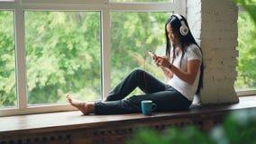 La morenita asiática linda de la muchacha se está sentando en travesaño de la ventana, está escuchando la música en auriculares y almacen de metraje de vídeo