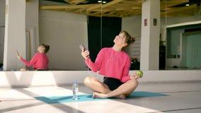La morenita atlética caucásica endereza ropa de deportes, mirando en un espejo almacen de video