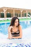 La morenita atractiva en el bikini blanco en el cuerpo delgado y bien proporcionado bronceado es relajante en la piscina Vocación foto de archivo libre de regalías