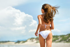 La morenita atractiva está corriendo en la playa, en un bikini blanco elegante Fotografía de archivo